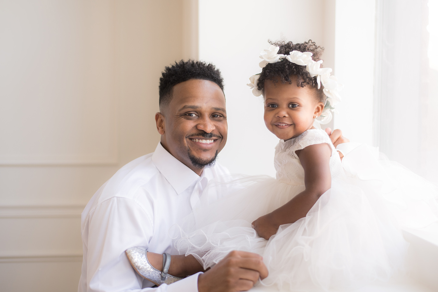 Chicago baby wears a white dress and takes a photo with her father.