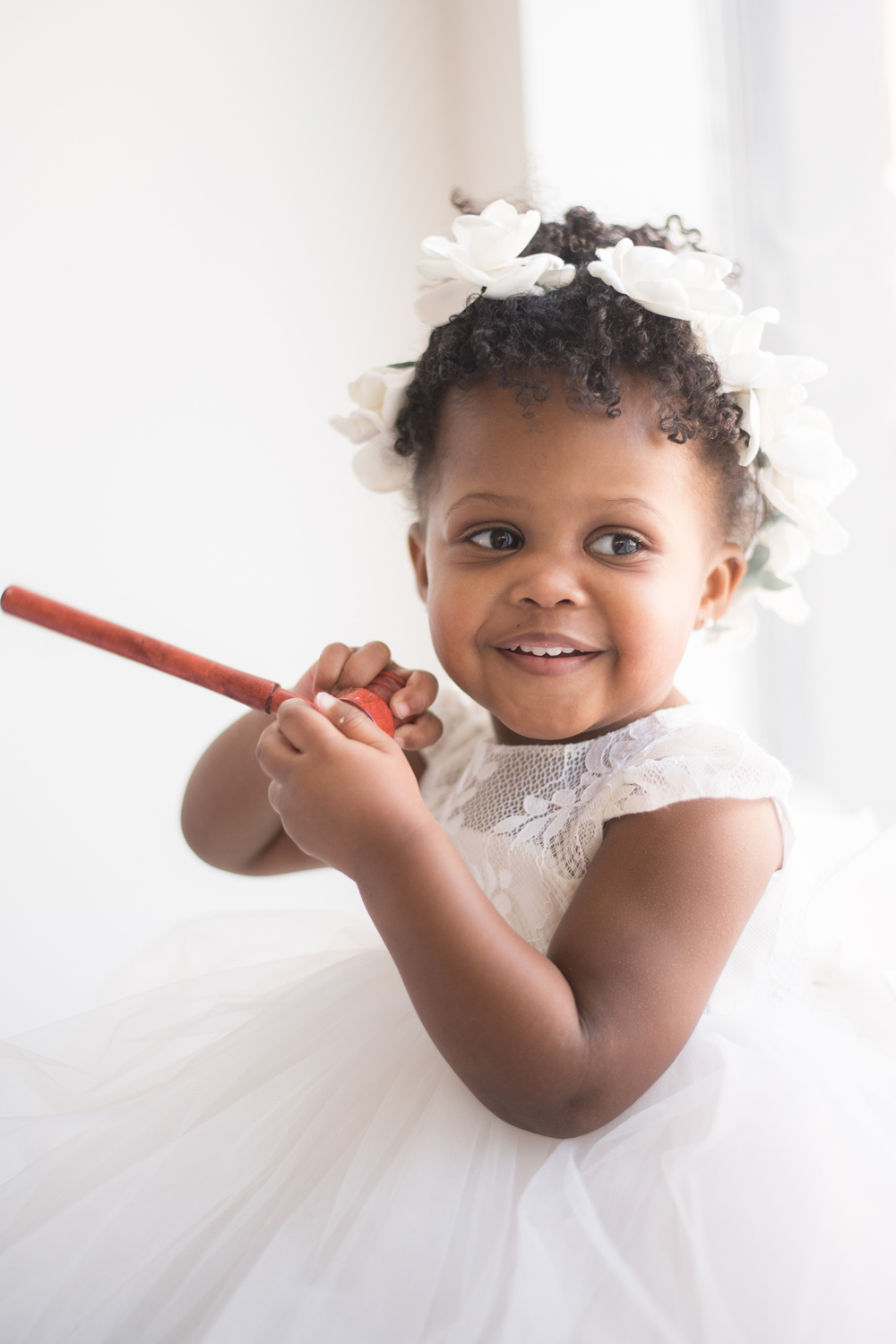 Two-year-old toddler plays with a miniature gavel and smiles.