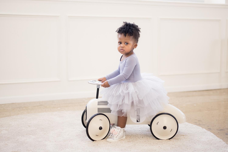 Sophia rides an antique miniature car in a grey tutu.
